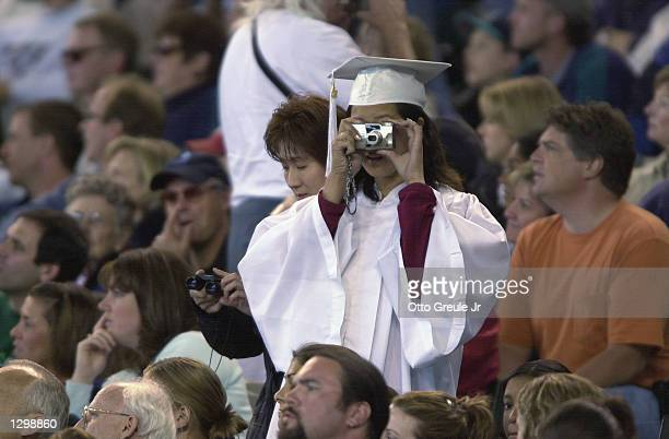 A recent graduate in cap and gown takes a picture of the field from the stands during the MLB game between the San Diego Padres and the Seattle...
