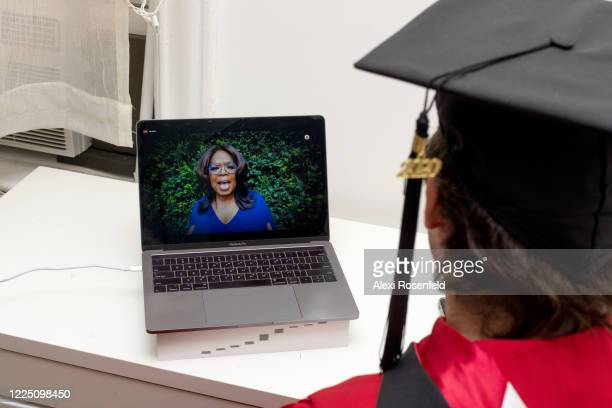 Recent graduate watches Oprah Winfrey speak during a virtual graduation ceremony held by Facebook from his laptop on May 15, 2020 in New York City....