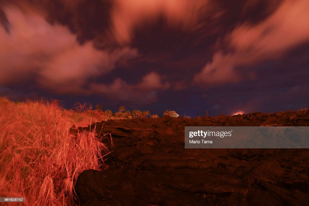 A recent lava flow (R), from a Kilauea volcano fissure, sits in a field at night on Hawaii's Big Island on May 22, 2018 in Kapoho, Hawaii. One week ago, prior to the lava flow, the area was open cow pasture.