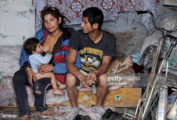 Recent picture of a young Roma family mother Alena Kalejova breastfeeding her baby Daniela next to the father Daniel Cervenak in their mudhut in...
