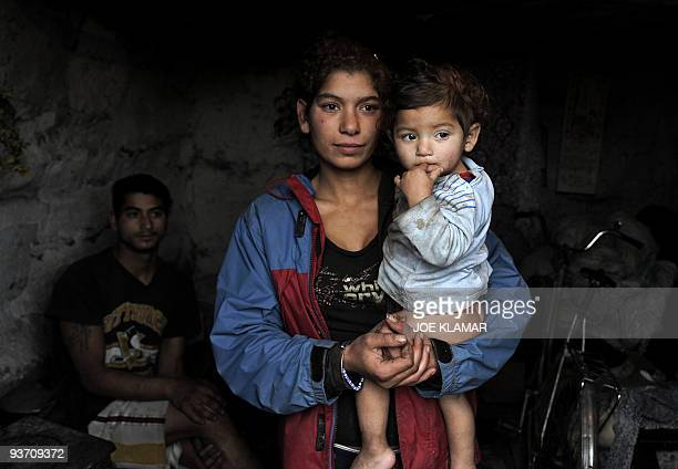 Recent picture of a young Roma family mother Alena Kalejova posing with her baby Daniela under the look of the father Daniel Cervenak in their mudhut...