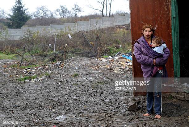 Recent picture of young Roma mother Alena Kalejova posing with her baby Daniela in front of a concrete panel wall dividing gypsy part of a village...