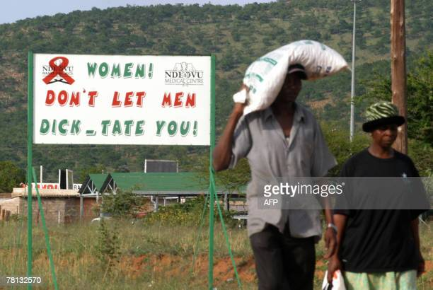 Recent picture showing South African residents passing one of the billboards carrying an HIV messageboard which were put up by the Ndlovu community...