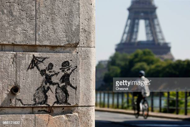 A recent work by street artist Banksy is seen on a wall next to the Eiffel Tower on June 27 2018 in Paris France The British artist Banksy confirmed...