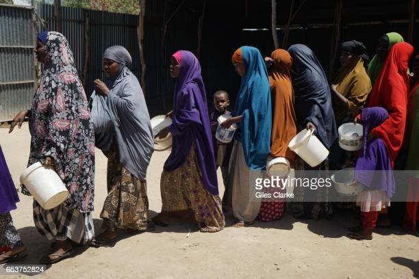 Recently arrived internally displaced women and children wait in a 'wetfood' line at a World Food Program center in Mogadishu Somalia Thousands of...
