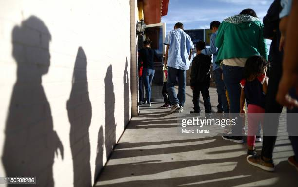 Recently arrived migrants from Central America line up to receive dinner at a church shelter for migrants who are seeking asylum on May 18 2019 in El...