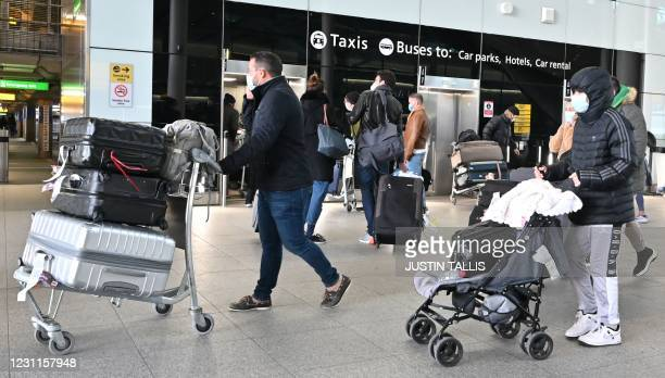 Recently arrived passengers with luggage wait for the lifts to the car parks and public transport at London Heathrow Airport in west London on...