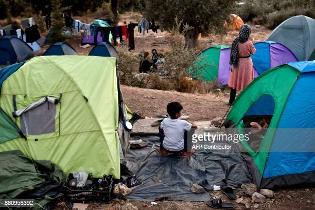Recently arrived refugees sit in a makeshift tent camp near the overcrowded hotspot on the Greek eastern Aegean islands of Samos on October 13 2017...