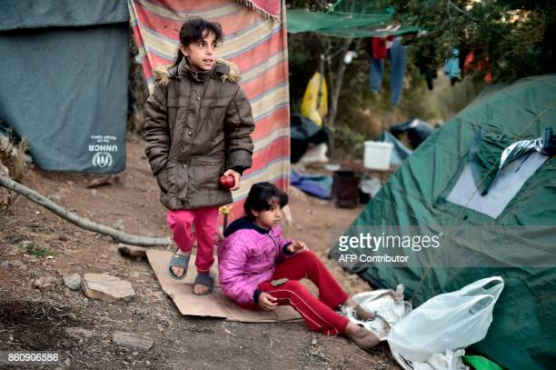 Recently arrived refugees walk at a makeshift tent camp near the overcrowded hotspot on the Greek eastern Aegean islands of Samos on October 13 2017...