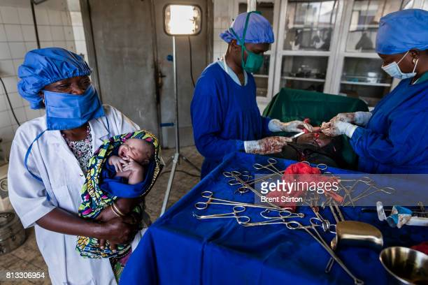 A recently delivered baby via emergency caesarian is seen in the arms of a Congolese nurse while doctors sew up the mother in the background Mutwanga...
