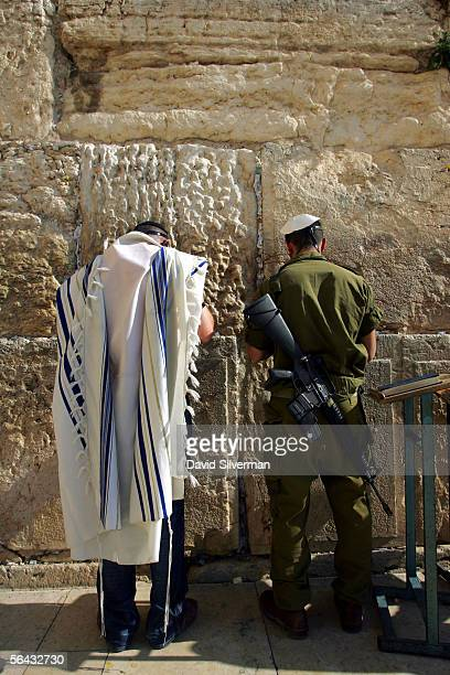 A recently drafted Israeli soldier and a modern Orthodox Jew pray next to each other at the Western Wall Judaism's holiest site December 14 2005 in...