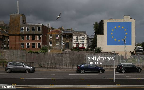 A recently painted mural by British graffiti artist Banksy depicting a workman chipping away at one of the stars on a European Union themed flag in...