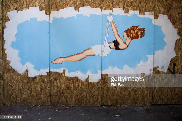 A recently painted mural of a woman in a mask on swing is displayed on boards during the coronavirus pandemic on May 03 2020 in San Francisco...