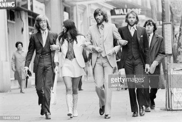 Recently reformed pop group the Bee Gees walking arminarm with Linda Gray London 21st August 1970 Left to right Robin Gibb Linda Gray Barry Gibb and...