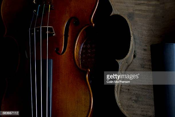 Recently-made violin on display with the casing of a damaged instrument at Andrew Hutchinson's workshop at Hoylake, Wirral, north west England. Mr...