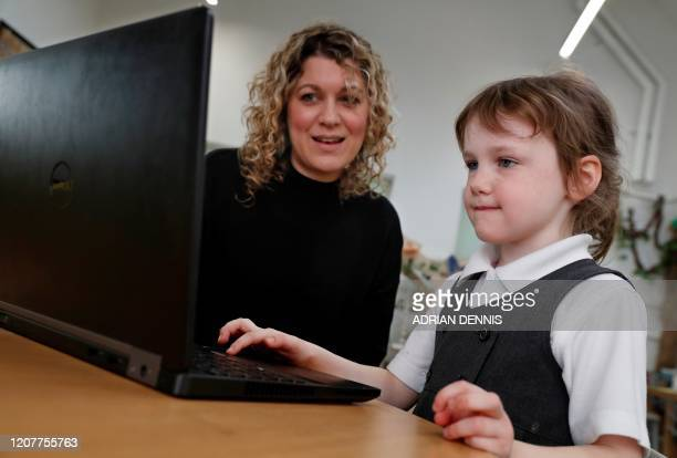 Reception class teacher Inez Horn poses for a photograph with five-year-old Ava Marshall, as she shows her how to use a laptop for online studying at...
