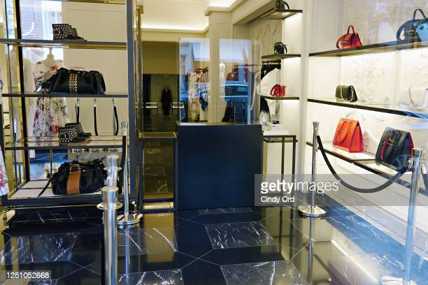 Reception desk with hand sanitizer and gloves is set up in the entrance of the Alexander McQueen store on Madison Avenue as the city moves into phase...