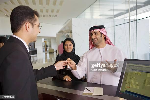Reception Staff Handing Keys to an Arab Couple. Dubai, United Arab Emirates