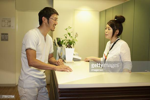 Receptionist and Man Standing at Reception Desk in Hairsalon