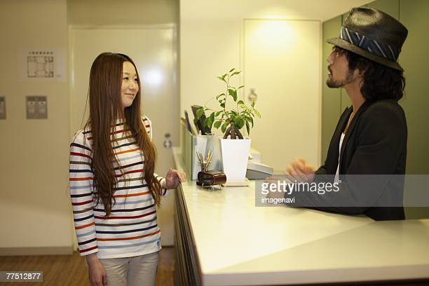 Receptionist and Woman Standing at Reception Desk in Hairsalon