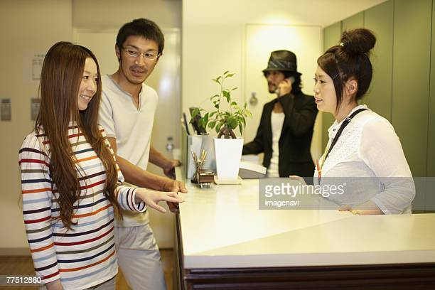 Receptionist and Young Couple Standing at Reception Desk in Hairsalon