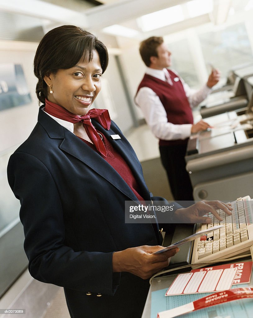 Receptionist at Airport Check-in Desk : Stock Photo
