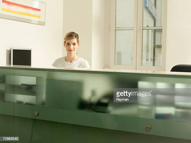 receptionist behind desk, dentist office - medical receptionist uniforms stock photos and pictures