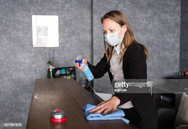 receptionist cleaning desk with disinfectant at reception - antiseptic wipe stock pictures, royalty-free photos & images