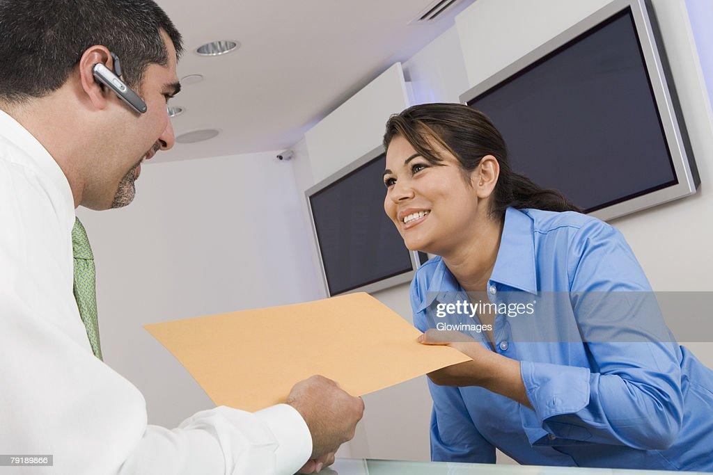 Receptionist giving a file to a businessman : Foto de stock