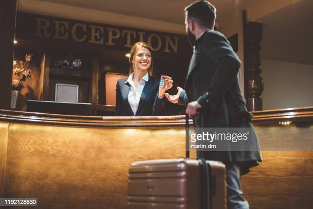 receptionist giving keys to hotel guest - hotel stock pictures, royalty-free photos & images