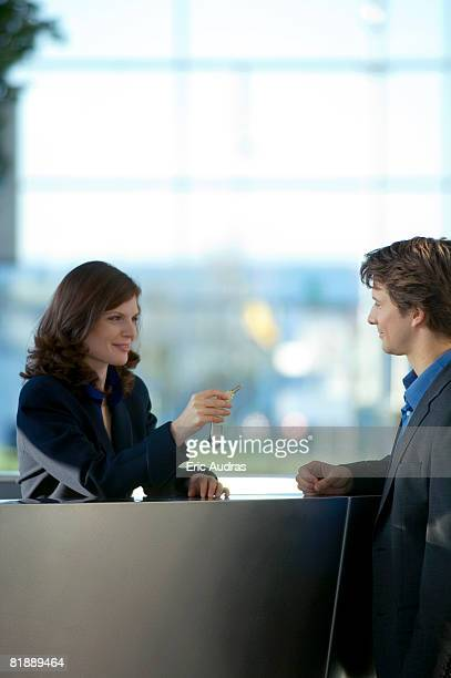 Receptionist giving the key of a hotel room to a businessman