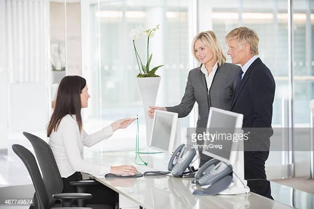 Bürorezeption geben Sie die Karte für Geschäftsleute In Büro