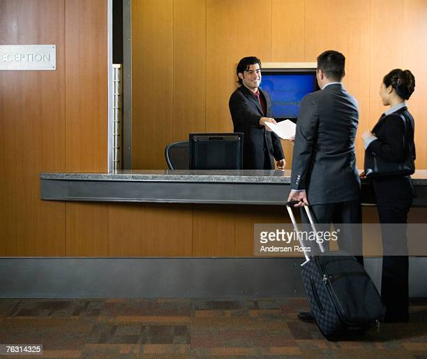 Receptionist greeting business travellers at reception desk
