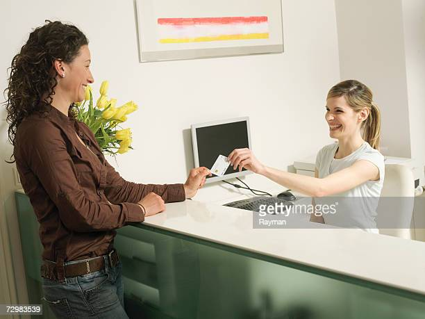 receptionist handing card to patient - medical receptionist uniforms stock pictures, royalty-free photos & images