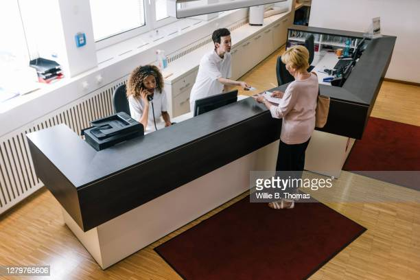 receptionist handing medical insurance card back to patient at mri clinic - medical receptionist uniforms stock pictures, royalty-free photos & images
