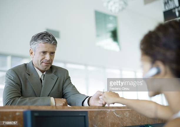 Receptionist handing something to man across counter