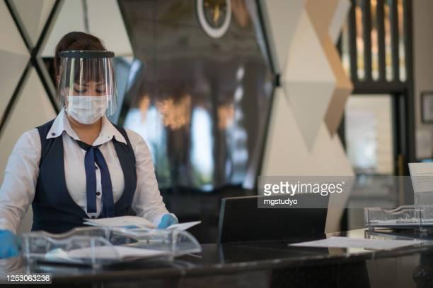 empfangsdame begrüßt ihre kundin mit schützender gesichtsmaske - hotel stock-fotos und bilder