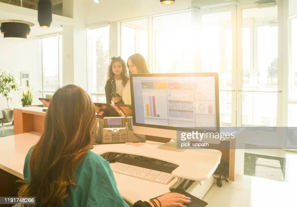 receptionist lobby with patients - receptionist stock pictures, royalty-free photos & images