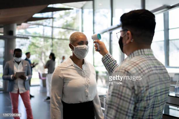 receptionist measuring temperature of female employee at office's entrance - with face mask - employee stock pictures, royalty-free photos & images