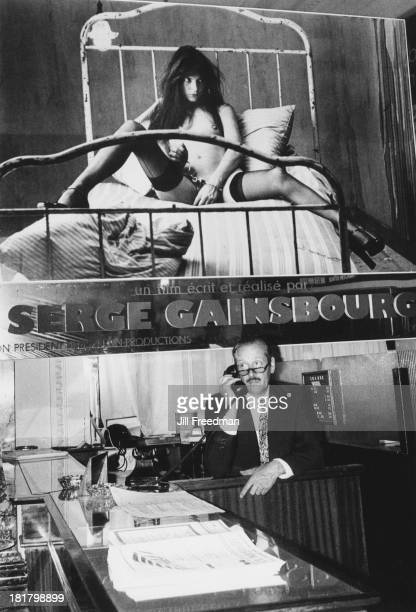 A receptionist on the front desk of a hotel sits beneath a poster showing Serge Gainsbourg's photograph of Jane Birkin taken for 'Lui' magazine...