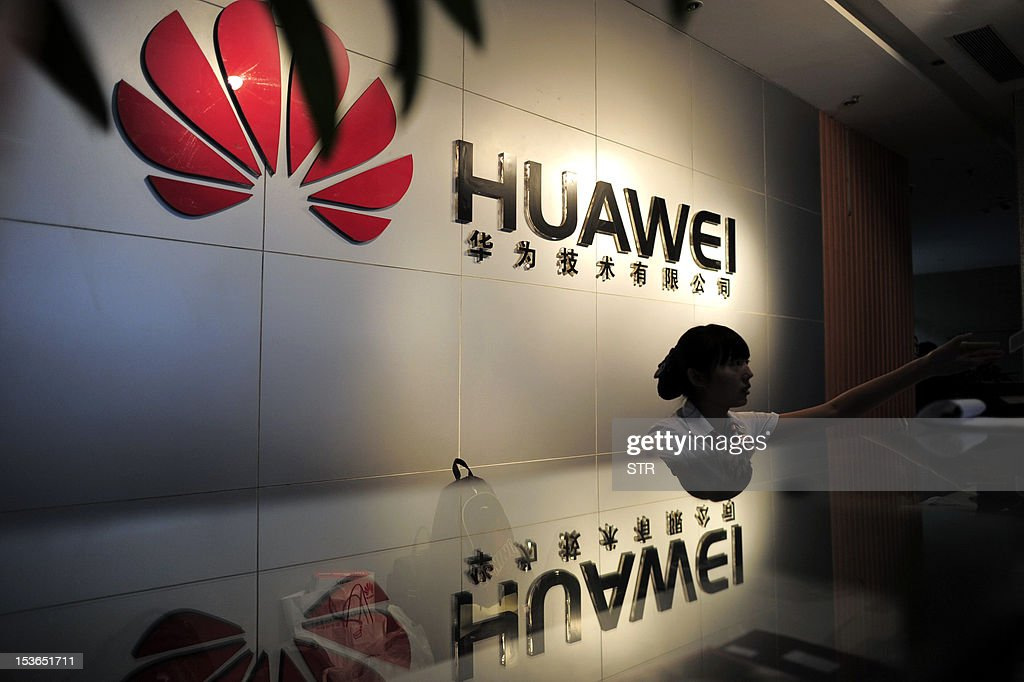A receptionist sits behind the counter at the Huawei office in Wuhan, central China's Hubei province on October 8, 2012. Beijing on October 8 urged Washington to 'set aside prejudices' after a draft Congressional report said Chinese telecom firms Huawei and ZTE were security threats that should be banned from business in the US. CHINA