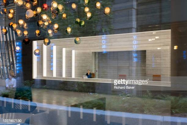 Receptionist sits in the foyer of corporate office space in the City of London, on 29th July 2020, in London, England.