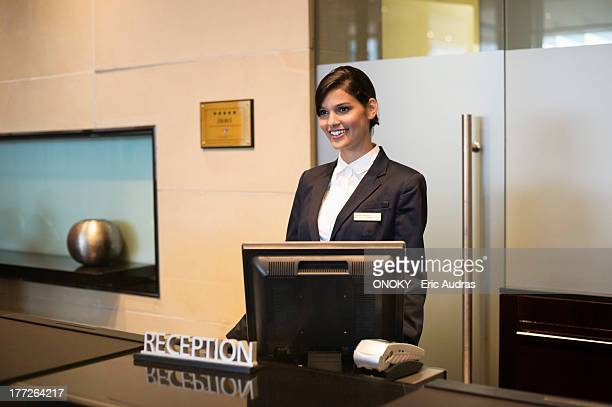 Receptionist standing at the hotel reception counter and smiling