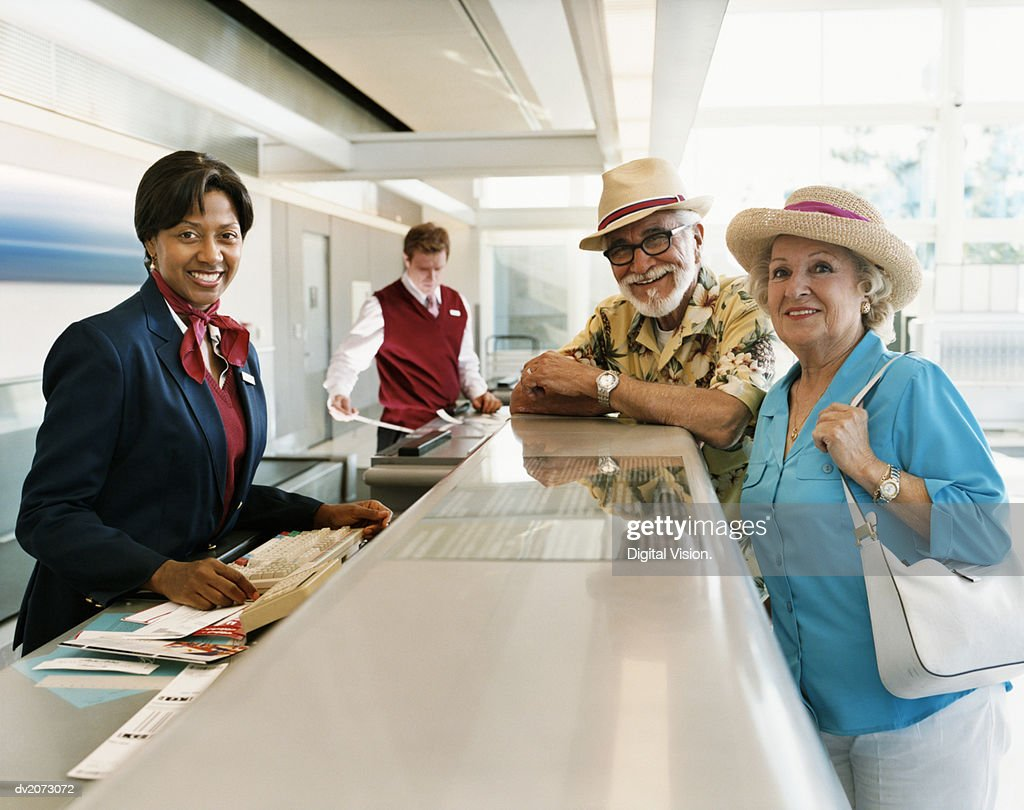 Receptionist Talking to Passengers at Airport Check-in Desk : Stock Photo