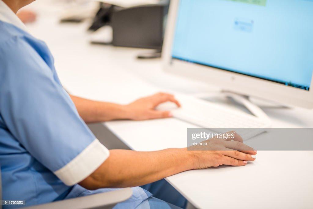 Receptionist using computer : Stock Photo