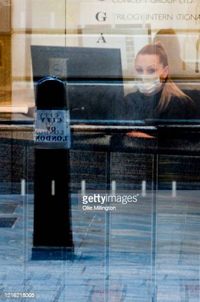 A receptionist wearing a mask in on of the few last places open in the City of London financial district on March 31 2020 in London England British...