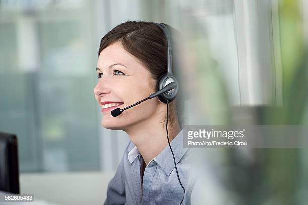 Receptionist wearing headset, smiling cheerfully