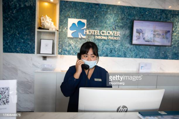 Receptionist wears a protective mask while speaking on the phone at Hotel Clover Patong Phuket in Patong, Phuket, Thailand, on Saturday, Dec. 19,...