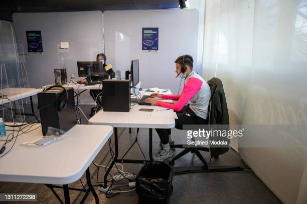 Receptionists answer calls in a centre for vaccination bookings inside the Paris Stade de France following its conversion into a Covid-19 vaccination...