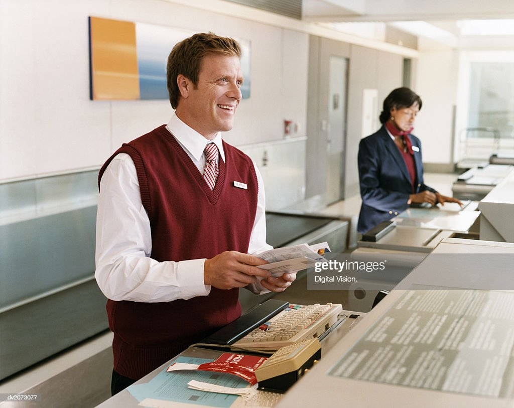 Receptionists at Airport Check-in Desk : Stock Photo